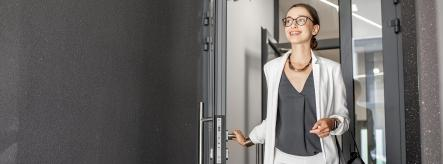Young woman walking through door - apprenticeship entry requirements