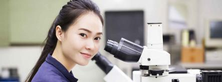 science student using a microscope at university