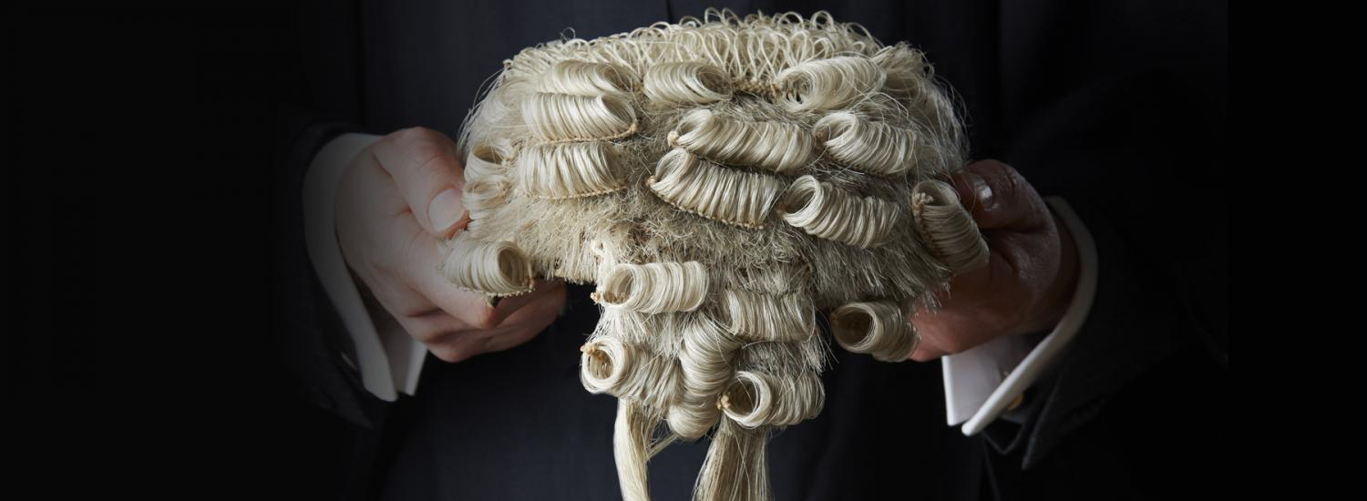 A barrister holding a wig