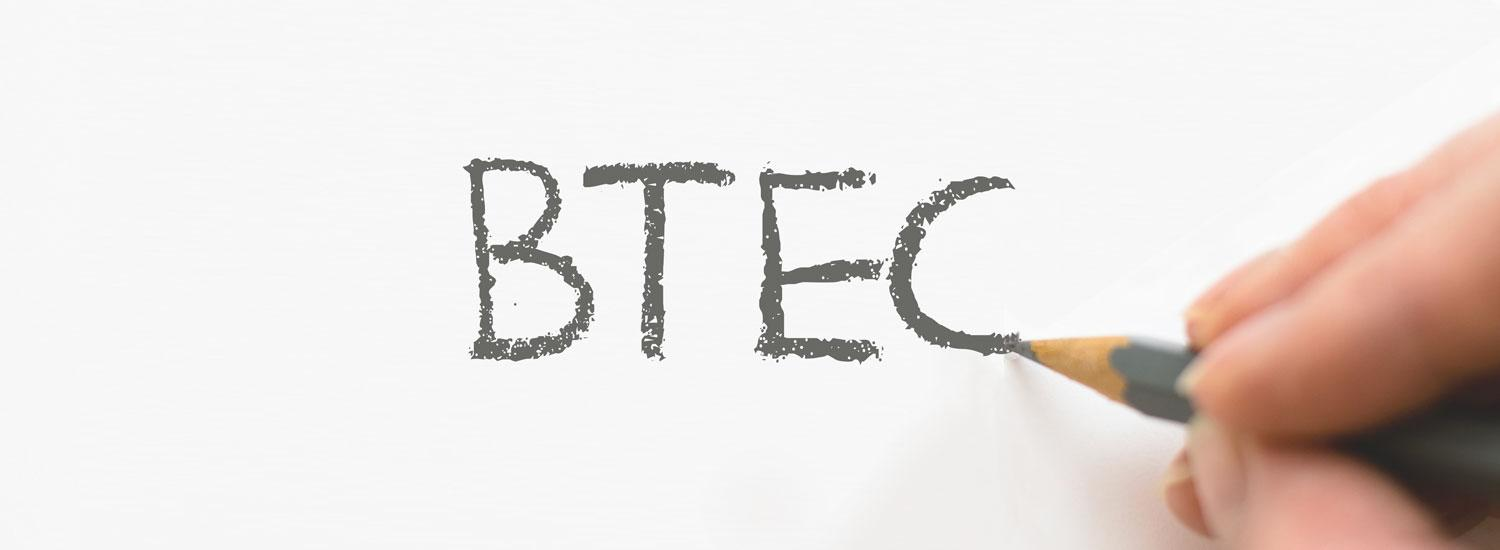 Person writing the word BTEC